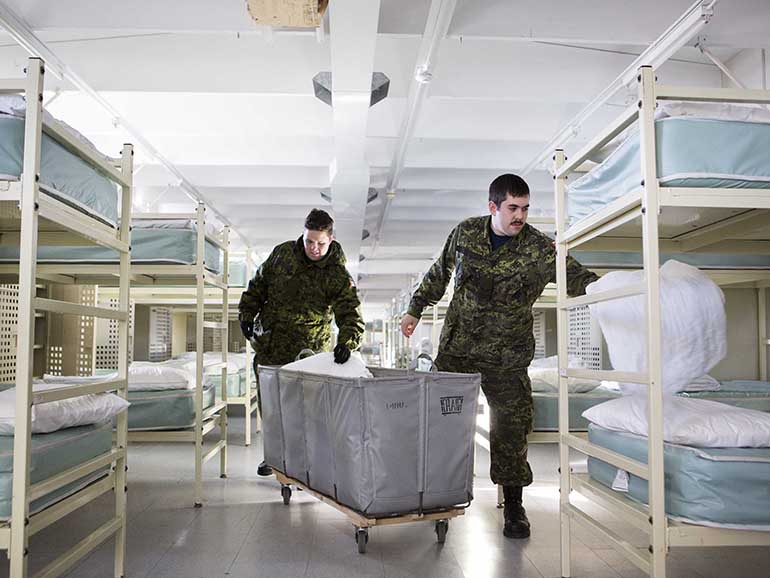 Aviators Mike Dudas (left) and Christopher Thomson put linens on the beds inside the barracks that will potentially be used by refugees at the Trenton Cadet Training Centre on CFB Trenton. (Photograph by Della Rollins)
