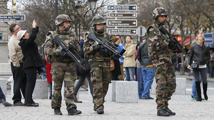 Tourists pause to take pictures as French military patrol near the Notre Dame Cathedral (not seen) the day after a series of deadly attacks in Paris, France, November 14, 2015. (Yves Herman/Reuters)