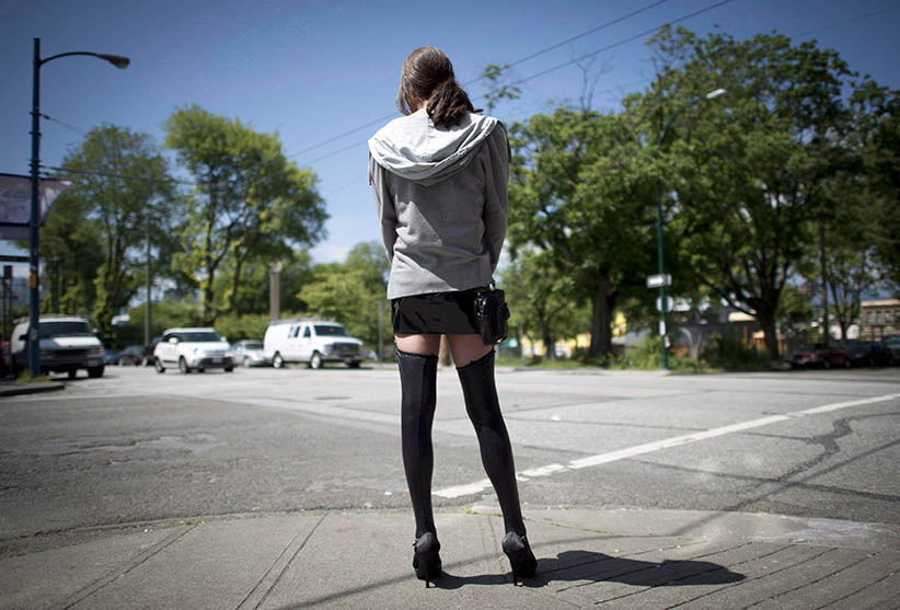 A sex trade worker is pictured in downtown Vancouver, onJune, 3, 2014. A new report by the Canadian Public Health Association calls on the government to regulate the sex industry as a business. (JONATHAN HAYWARD/CP)