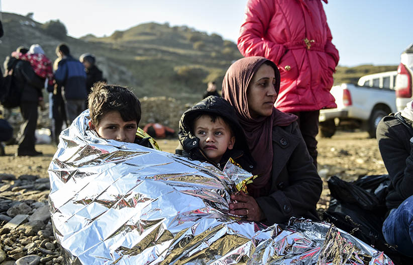 A Syrian family waits after arriving on the Greek island of Lesbos along with other migrants and refugees, on November 17, 2015, after crossing the Aegean Sea from Turkey.  At least eight people drowned when a boat carrying migrants from Turkey sank off the Greek island of Kos, the coastguard said on November 17, 2015. They were the latest of nearly 3,500 deaths at sea this year among people making desperate bids to flee war and poverty and to reach Europe, according to UN figures. European leaders tried to focus on joint action with Africa to tackle the migration crisis, as Slovenia became the latest EU member to act on its own by barricading its border. (BULENT KILIC/AFP/Getty Images)