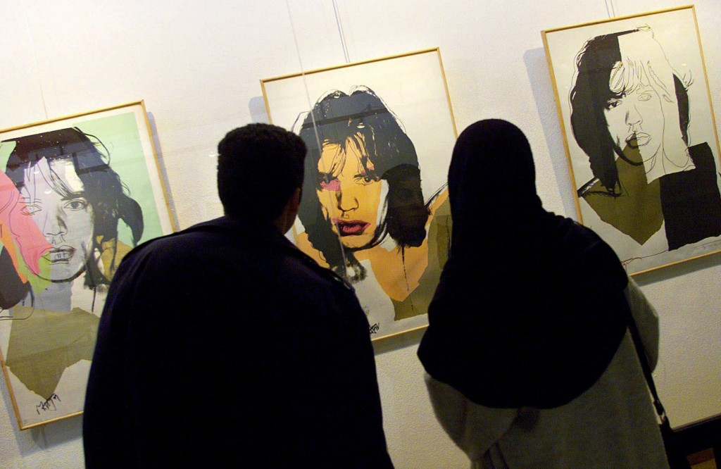 Iranians look at Andy Warhol's portraits of rock star Mick Jagger during an exhibition of Pop Art at the Museum of Contemporary Art in Tehran, Iran, Feb. 20, 2000. (AP photo/Enric Marti)
