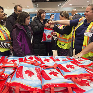 Newly-arrived Syrian refugee Anjilik Jaghlassian, centre, and her family receive winter clothes and other items at Pearson International airport, in Toronto, on Friday, Dec. 11, 2015. (Nathan Denette/CP)