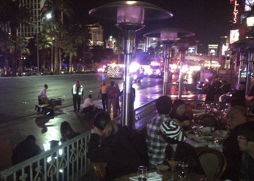 People crowd on a sidewalk while police cars and ambulances gather on a street after a car drove onto a busy sidewalk and mowed down people outside a casino in Las Vegas, NV., Sunday, Dec. 20, 2015. A woman intentionally swerved her car onto a busy sidewalk two or three times and mowed down people outside a Las Vegas casino, police said. (Justin Cochrane via AP) MANDATORY CREDIT