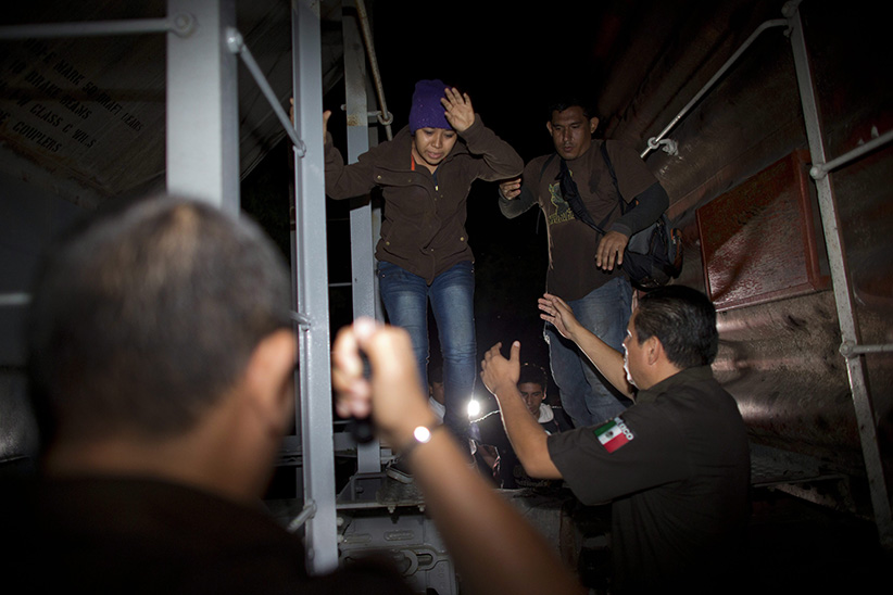 "Immigration officials remove Central American migrants from a northbound freight train during an after midnight raid by federal police in San Ramon, Mexico. Following a surge in child migrants reaching the U.S. border in 2014, Mexican authorities said Tuesday, March 3, 2015 that they staged more than 150 raids over the last year on the train known as ""La Bestia"" that rolled toward the U.S. border crowded with hundreds of Central American migrants. (Rebecca Blackwell/AP)"
