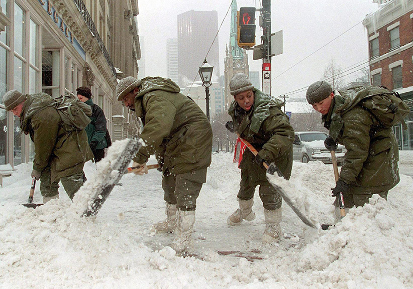 Members of the Royal Canadian Regiment (from left to right) Pte. Paul Roventa, Master Cpl. Gary Walters, Cpl. Cameron Kerryann, and Pte. Phil Cheung shovel snow in downtown Toronto Friday, Jan.15, 1999. Ten years after a series of winter storms buried Toronto under more than a metre of snow, former mayor Mel Lastman still takes pride in calling on the military to tackle clogged city streets while large swaths of wintry Canada looked on in wonder. (Kevin Frayer/CP)