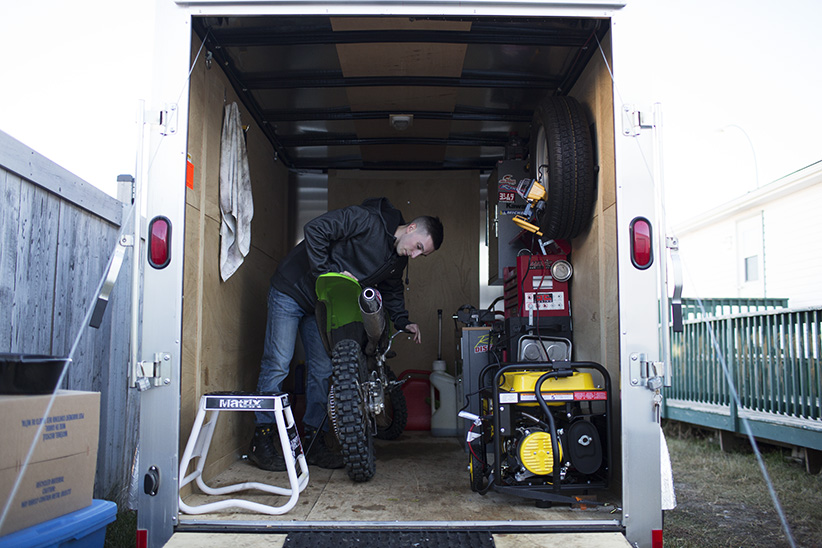 Brandon MacKay works on this motorbike in his trailer turned into a make shift garage, in Fort McMurray Alberta, November 14, 2015. Brandon MacKay was recently laid off from his job. (Photograph by Jason Franson)
