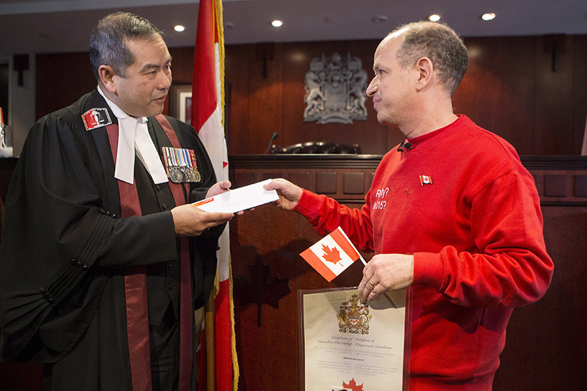 Dror Bar-Natan (right) hands a letter to Judge Albert Wong to disavow the portion of the oath that pertains to the Queen following a citizenship ceremony in Toronto on Monday November 30, 2015. (Chris Young/CP)