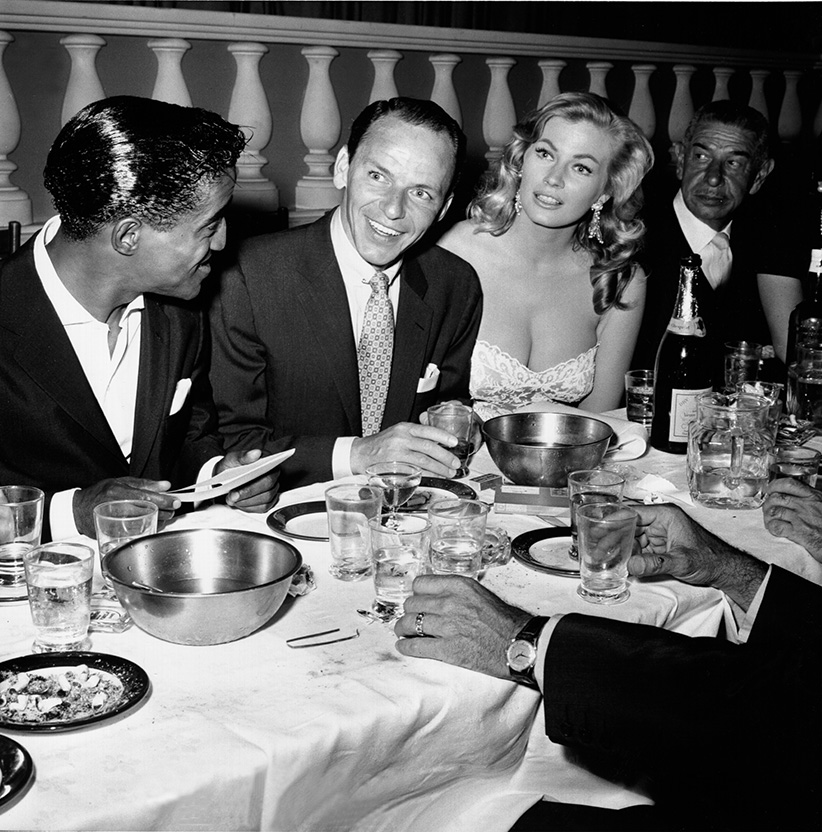 Singer and member of the Rat Pack Sammy Davis Jr., Frank Sinatra, actress Anita Ekberg and restauranteur Mike Romanoff dine at Romanoff's Restaurant on August 1, 1955 in Los Angeles, California. (Earl Leaf/Michael Ochs Archives/Getty Images)
