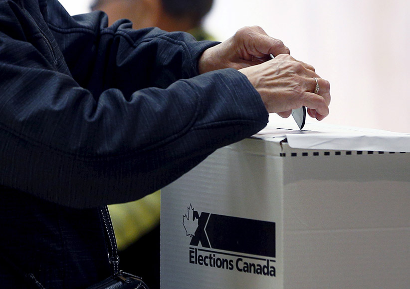A voter casts her ballot at a polling station in Quebec City, October 19, 2015. (Mathieu Belanger/Reuters)