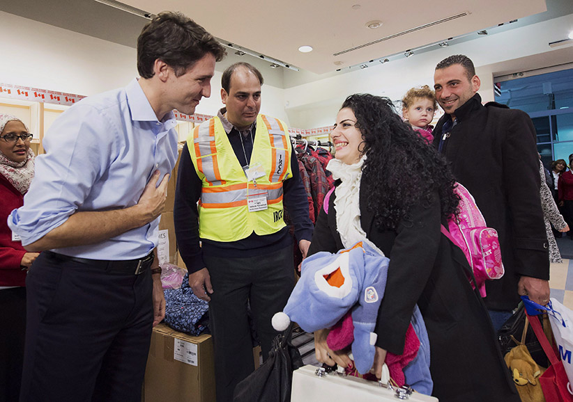 Canadian Prime Minister Justin Trudeau, left, greets new Syrian refugees Georgina Zires, centre, 16 month-old Madeleine Jamkossian, second right, and her father Kevork Jamkossian at Pearson International airport in Toronto on Friday, December 11, 2015. (Nathan Denette/CP)