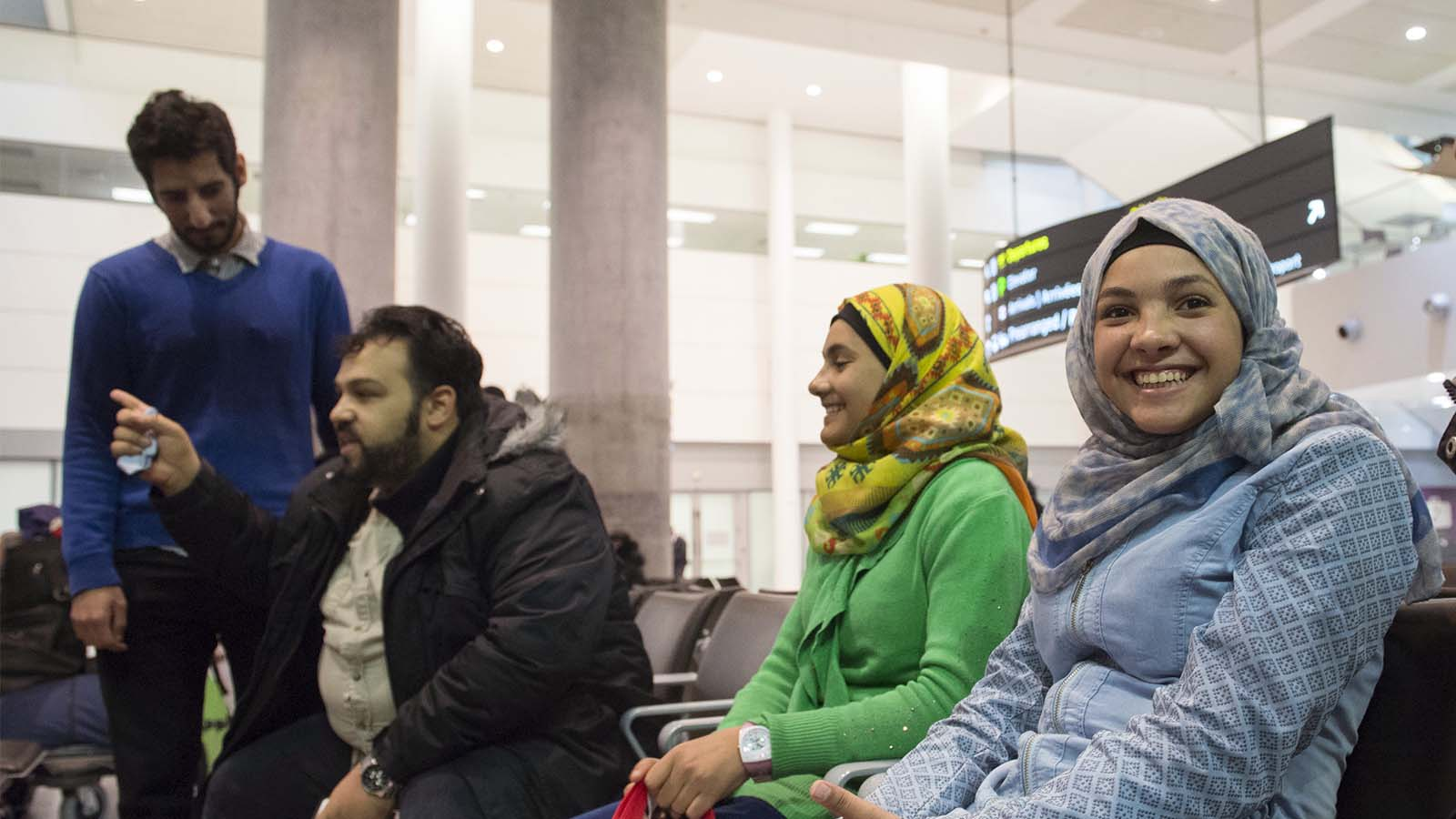 Syrian refugee siblings Rama, right, Riem, and Raniem take a rest with translators Bassam Alolayan, left, and Mohammad Samkari, at the Toronto Pearson International Airport after arriving from Frankfurt, Germany on Thursday, Dec. 10, 2015.  Photo by Hannah Yoon