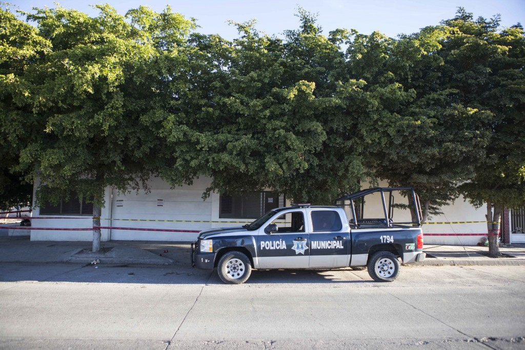 "A police truck sits parked outside the home where marines engaged in a gun battle during the search for Mexican drug lord Joaquin ""El Chapo"" Guzman, in Los Mochis, Mexico, Sunday, Jan. 10, 2016. Guzman apparently fled from the home Friday before authorities eventually caught him. A month or two of intensive renovations transformed the house, which is completely obscured by the tops of thick trees, into a completely enclosed structure, with its new walls advancing to the sidewalk. (AP Photo/Christian Palma)"