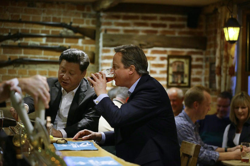 Britain's Prime Minister David Cameron, right, drinks a pint of beer with Chinese President Xi Jinping, centre,  at a pub in Princess Risborough near Chequers, England, Thursday, Oct. 22, 2015. (AP Photo/Kirsty Wigglesworth, pool)