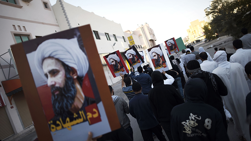Bahraini protesters hold placards bearing portraits of prominent Shiite Muslim cleric Nimr al-Nimr during clashes with riot police in the village of Sitra, south of the capital Manama, on January 8, 2016, following a protest against his execution by Saudi authorities. (Mohammed al-Shaikh/AFP/Getty Images)