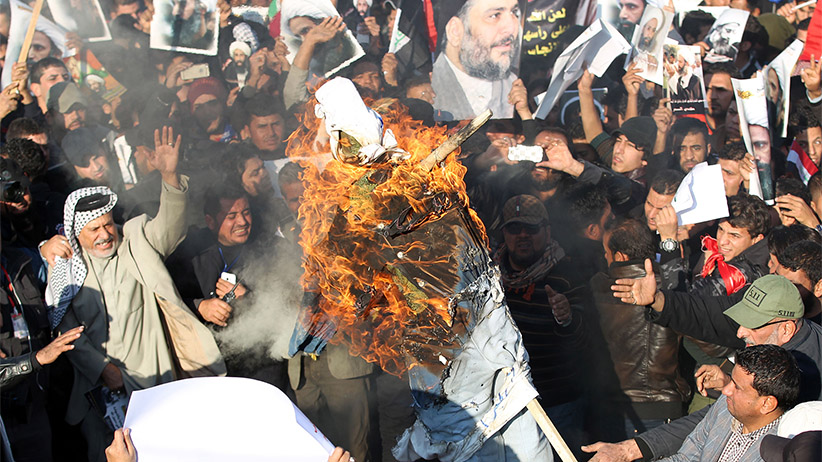 Supporters of Iraqi Shiite cleric Moqtada al-Sadr (portrait top-C) burn a effigy of a member of the Saudi ruling family as others hold posters of prominent Shiite cleric Nimr al-Nimr during a demonstration in the capital Baghdad on January 4, 2016, against Nimr's execution by Saudi authorities. Sunni-ruled Saudi Arabia severed diplomatic ties with Shiite-dominated Iran, its long-time regional rival, after angry demonstrators attacked the Saudi embassy in Tehran and its consulate following Nimr's execution. AHMAD AL-RUBAYE/AFP/Getty Images
