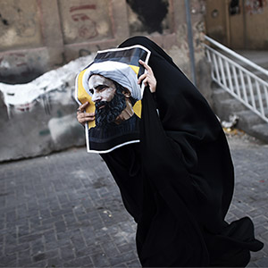 TOPSHOT - A Bahraini woman holds a poster bearing a portrait of prominent Shiite Muslim cleric Nimr al-Nimr during a protest against his execution by Saudi authorities, in the village of Jidhafs, west of the capital Manama on January 3, 2016. Iraq's top Shiite leaders condemned Saudi Arabia's execution of Nimr, warning ahead of protests that the killing was an injustice that could have serious consequences. MOHAMMED AL-SHAIKH/AFP/Getty Images
