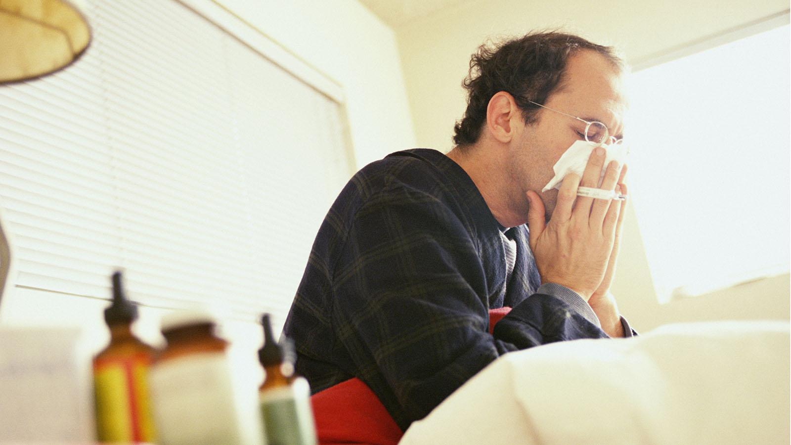 Man sick in bed blowing his nose.  Marc Romanelli/Getty Images