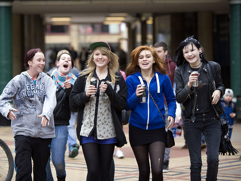 Teenage girls singing as they walk through the shopping precinct drinking Monster energy drinks in the Broadgate shopping precinct, Coventry. (John Harris/REPORT DIGITAL-REA/Redux)