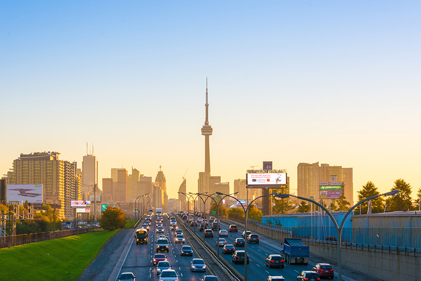 Toronto skyline from the Gardiner expressway entering the city during afternoon with CN Tower and other buildings in the background and two way traffic in the foreground. (Roberto Machado Noa/LightRocket/Getty Images)