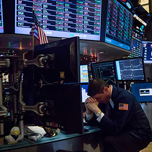 A trader bows his head while working on the floor of the New York Stock Exchange (NYSE) in New York, U.S., on Monday, Jan. 4, 2016. U.S. stocks tumbled to start 2016, falling to their lowest levels since mid-October, as a rout in Chinese equities renewed concern that an economic slowdown there will damp global growth. Photographer: Michael Nagle/Bloomberg/Getty Images