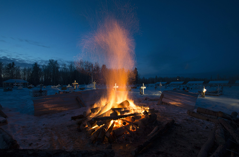 A fire burns as it thaws the frozen ground in order to dig a grave for one of the shooting victims at the cemetery in La Loche, Saskatchewan, Monday, Jan. 25, 2016. A 17-year-old was charged with first-degree murder and attempted murder in a mass shooting at a school and home in the remote aboriginal community in western Canada on Friday, officials said. (Jonathan Hayward/CP)
