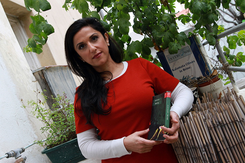 "Israeli author Dorit Rabinyan poses with her Hebrew-language novel titled ""Gader Haya"" (known in English as ""Borderlife"") on December 31, 2015 at her house in the coastal city of Tel Aviv. Israels Education Ministry Naftali Bennett has disqualified Rabinyan's novel, that describes a love story between an Israeli woman and a Palestinian man, for use in advanced literature classes in Israeli high schools.  (Gil Cohen/AFP/Getty Images)"