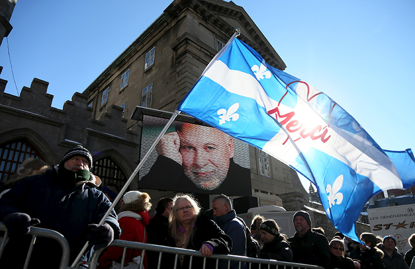 Celine Dion fan Adam St-Couer (L) holds a Quebec flag as he waits in line to be admitted for the funeral for Rene Angelil at Notre Dame Basilica in Montreal January 22, 2016. (Christinne Muschi/Reuters)