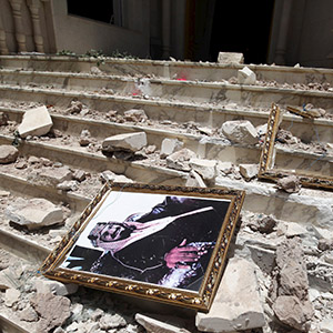 A picture of Saudia Arabia's King Salman bin Abdulaziz lies amidst debris at the damaged entrance to the headquarters of the Saudi Cultural Center in Sanaa, caused by an April 20 air strike that hit a nearby army weapons depot, in Sanaa April 21, 2015. REUTERS/Mohamed al-Sayaghi - RTX19NNH