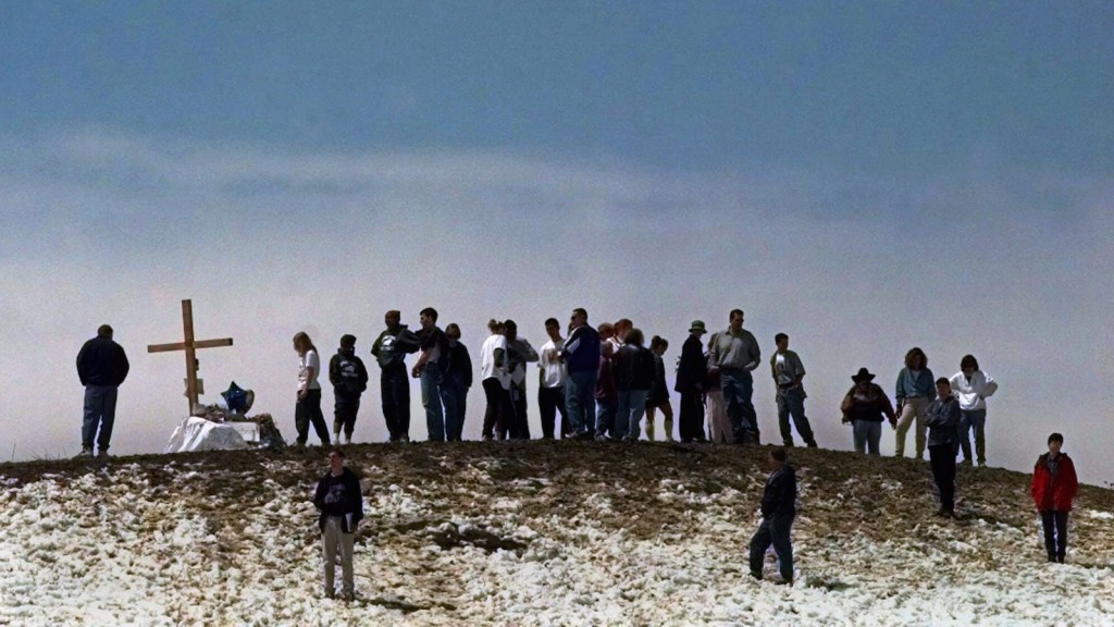 In this Saturday, April 24, 1999 file photo, mourners gather on top of a hill overlooking Columbine High School in Littleton, Colo. A total of 15 people, including gunmen Eric Harris and Dylan Klebold, died in the attack at the school. (AP Photo/Eric Gay)
