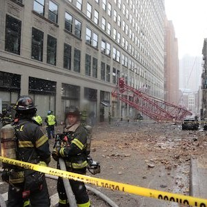 A collapsed crane lies on the street on Friday, Feb. 5, 2016, in New York.  The crane landed across an intersection and stretched much of a block in the Tribeca neighborhood, about 10 blocks north of the World Trade Center. There was damage to the roof of a nearby building, and debris littered the street. (AP Photo/Bebeto Matthews)