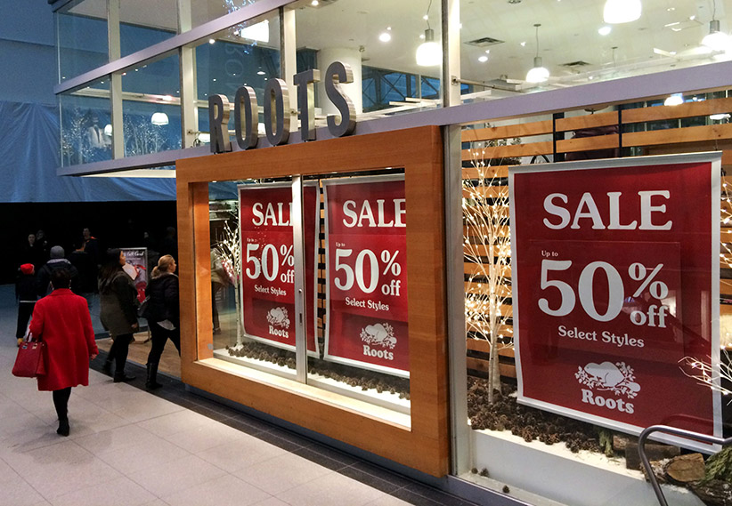 Pre-Christmas sale signs are prominent in the windows of Canadian retailer Roots at the Eaton Centre in Toronto, Ont., Dec. 21, 2015. (Rachel Verbin/CP)