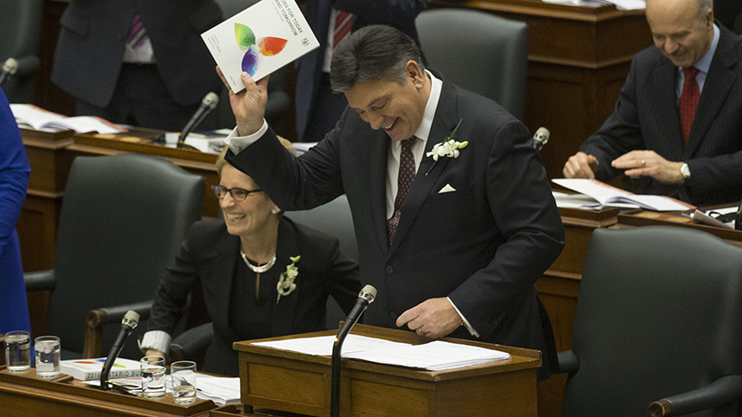 Minister of Finance Charles Sousa (right) shows off the budget to the Opposition benches as Premier Kathleen Wynne looks over the aisle. The Ontario Liberals table the budget in the Legislature. (Rick Madonik/Toronto Star/Getty Images)