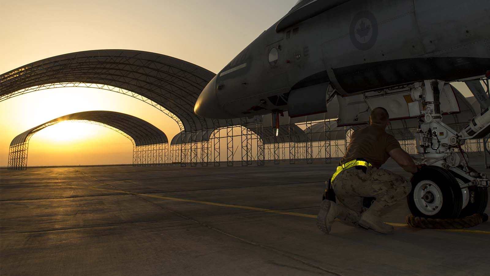 An aircraft technician from Air Task Force – Iraq inspects the nose landing gear of a CF-188 Hornet aircraft at the Camp Patrice Vincent flight line, in Kuwait during Operation IMPACT on December 11, 2015. (Canadian Forces Combat Camera)