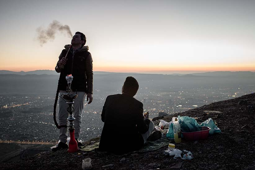 "Hawkar, 21, and Muhammad, 18, smoke shisha and picnic on a mountain overlooking the city of Sulaymaniyah in Iraqi Kurdistan. When asked about the economic situation in Kurdistan, Hawker says ""All the young people in Suli (Sulaymaniyah) are jobless and don't have money. If you go to the cafe. They don't have dinar in their pocket."" (Photograph by Cengiz Yar)"