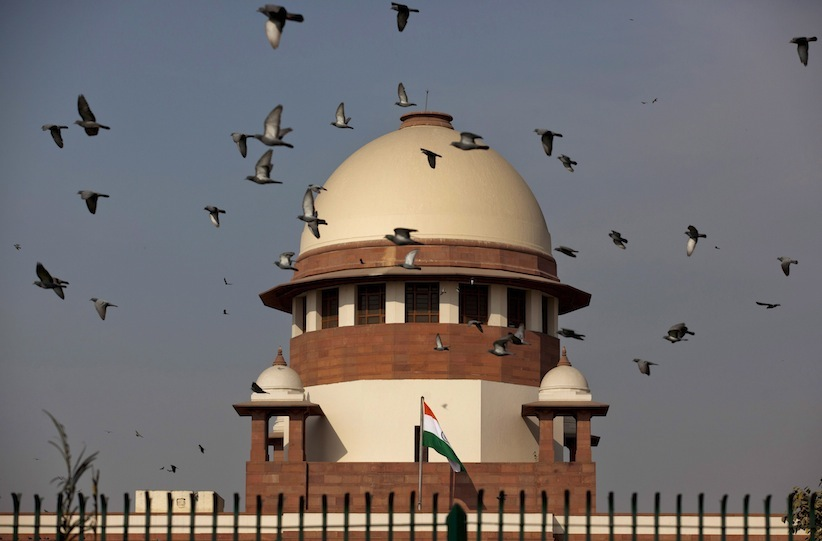 Pigeons fly past the dome of India's Supreme Court building in New Delhi, India, Tuesday, Feb. 2, 2016. (AP Photo/Tsering Topgyal)