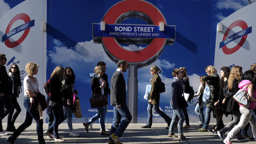 People walk past signs for a London Underground improvement programme during a busy afternoon on Oxford Street in London May 3, 2014. A second tube strike is planned to go ahead on May 5. REUTERS/Kevin Coombs
