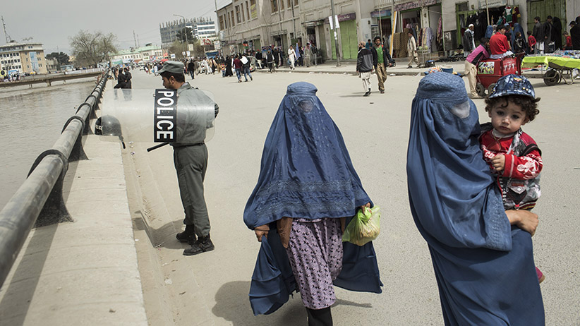Afghanistan, Kabul, March 27, 2015. Burqa-clad women walk past Afghan riot police next to the Kabul river close to the spot where last week the 27-year old woman Farkhunda was murdered by a mob after she was falsely accused of burning a Koran. The police is expecting demonstration to ask for justice of the killers. (Joel van Houdt)