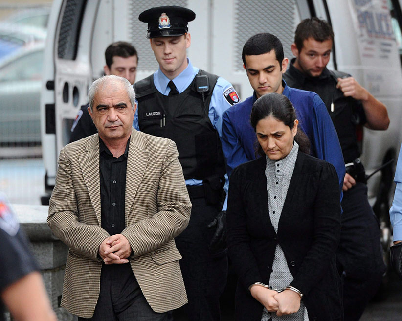 Tooba Mohammad Yahya and husband Mohammad Shafia and their son Hamed Mohammed Shafia are escorted by police officers into the Frontenac County Court courthouse on the first day of trial in Kingston, Ontario on Thursday, October 20, 2011. (Sean Kilpatrick/CP)