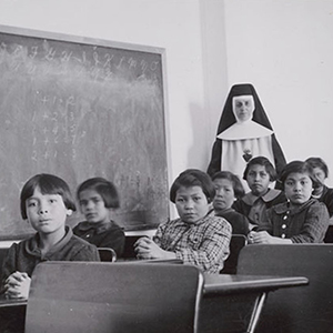 "A group of female students and a nun pose in a classroom at Cross Lake Indian Residential School in Cross Lake, Manitoba in a February 1940 archive photo. A Canadian policy of forcibly separating aboriginal children from their families and sending them to residential schools amounted to ""cultural genocide,"" a six-year investigation into the now-defunct system found on June 2, 2015. The residential school system attempted to eradicate the aboriginal culture and to assimilate aboriginal children into mainstream Canada, said the long-awaited report by the Truth and Reconciliation Commission of Canada. (Library and Archives Canada/Reuters)"