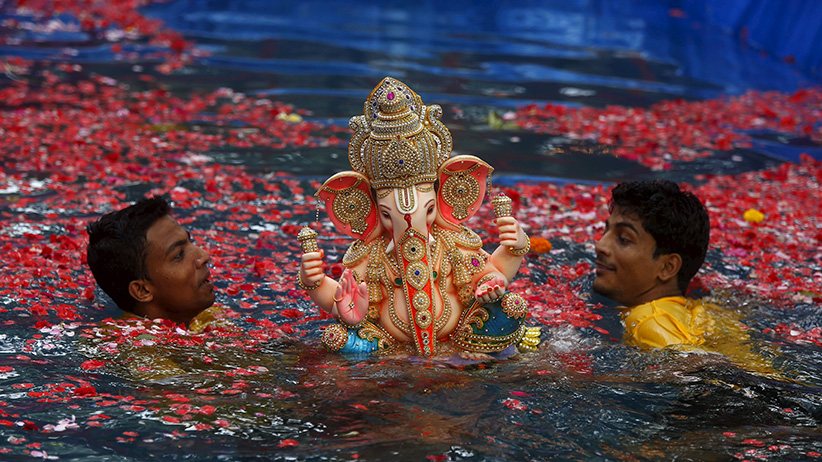 Volunteers carry an idol of the Hindu elephant god Ganesh, the deity of prosperity, in a pond for its immersion during the ten-day-long Ganesh Chaturthi festival in Mumbai, India, September 18, 2015. During the festival, idols are taken through the streets in a procession accompanied by dancing, singing and later immersed in a river or the sea in accordance with the Hindu faith. (Shailesh Andrade/Reuters)