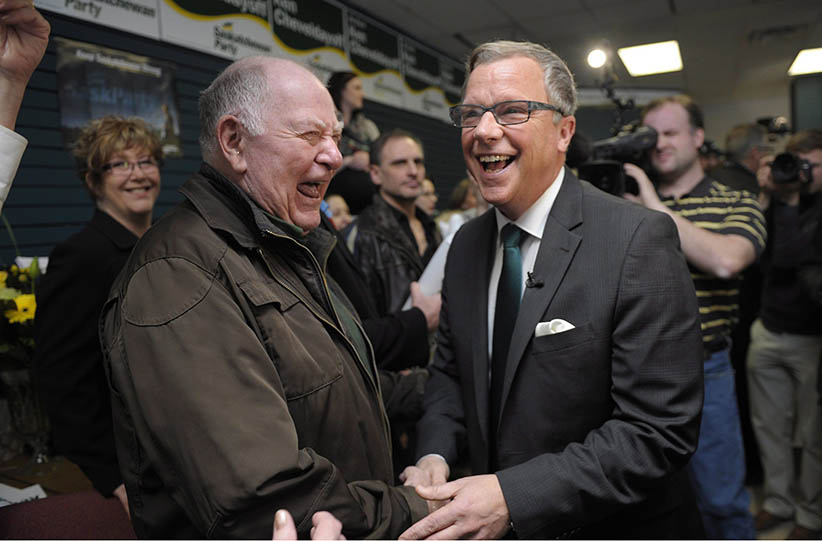 Brad Wall, right, shares a laugh with supporter Ross Huckle, left, during the Saskatchewan Party's election campaign kick-off in Saskatoon, Saskatchewan on Tuesday March 8, 2016. (Michael Bell/CP)