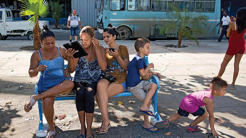 From left to right Miriellis Toirac, Jenny Pinientel and Wendy Martinez along with their children, connecting to Wifi at the Estadio Latinoamericano. Where Obama will throw out the first pitch  on March 22nd and a new wifi spot has been installed.