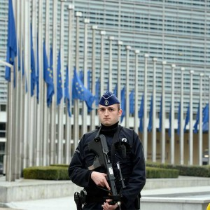 A Belgian Police officer stands guard in front of the European Union Commission headquarter in Brussels where the European flags are seen at half mast, after the terrorists attacks at Brussels airport and in the Brussels metro, 22/03/2016. (Thierry Charlier/Camera Press/Redux)
