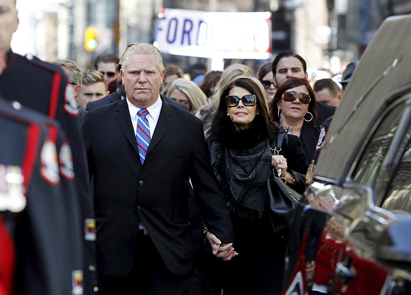 Doug Ford and his wife walk behind the hearse carrying former Toronto Mayor Rob Ford to St James Cathedral for funeral services in Toronto, March 30, 2016. (Fred Thornhill/Reuters)