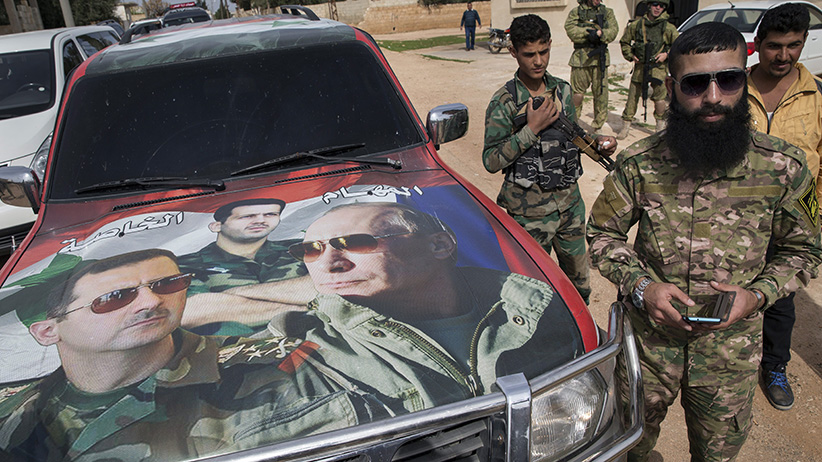 Syrian solders and Russian solders, who escort a group of journalists in the background, stand near a car covered by collage showing photos of faces of Russian President Vladimir Putin, right, Syrian President Bashar Assad, left, and a Syrian general, President's Assad brother, Maher Assad, center, in Maarzaf, about 15 kilometers west of Hama, Syria, Wednesday, March 2, 2016. (Pavel Golovkin/AP)