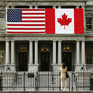 A woman stops to take a photo of the U.S. and Canadian flags placed side-by-side on the Eisenhower Executive Office Building next to the White House in Washington March 8, 2016.  Preparations are under way for the official state visit of Canada's Prime Minister Justin Trudeau on Thursday. (Kevin Lamarque/Reuters)