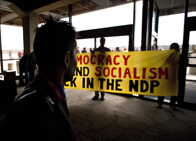 NDP delegates show a banner during the 2016 NDP Federal Convention in Edmonton Alta, on Sunday, April 10, 2016. THE CANADIAN PRESS/Jason Franson