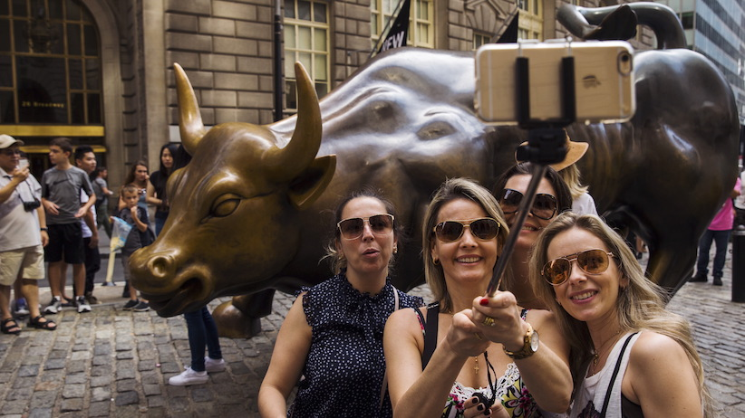 Tourists pose for photographs with a landmark statue of a bull in New York REUTERS/Lucas Jackson