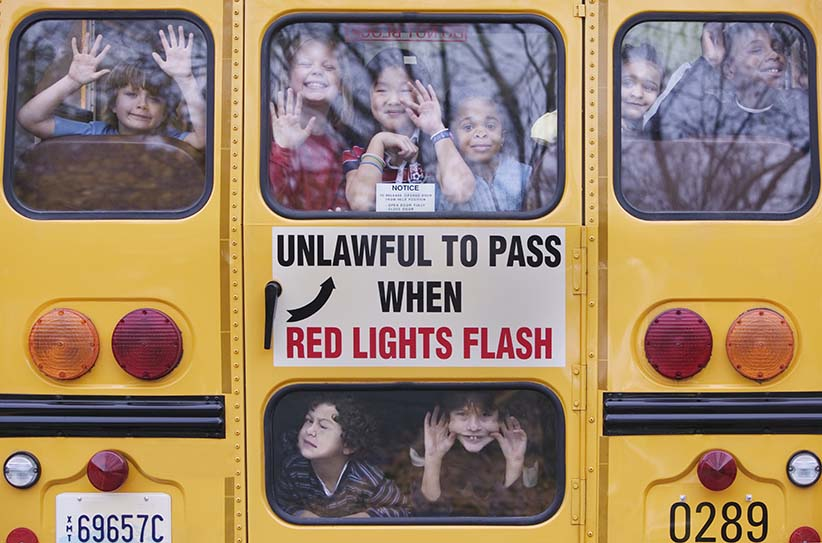 Kids Looking Out Rear Window of School Bus. (Andersen Ross/Getty Images)