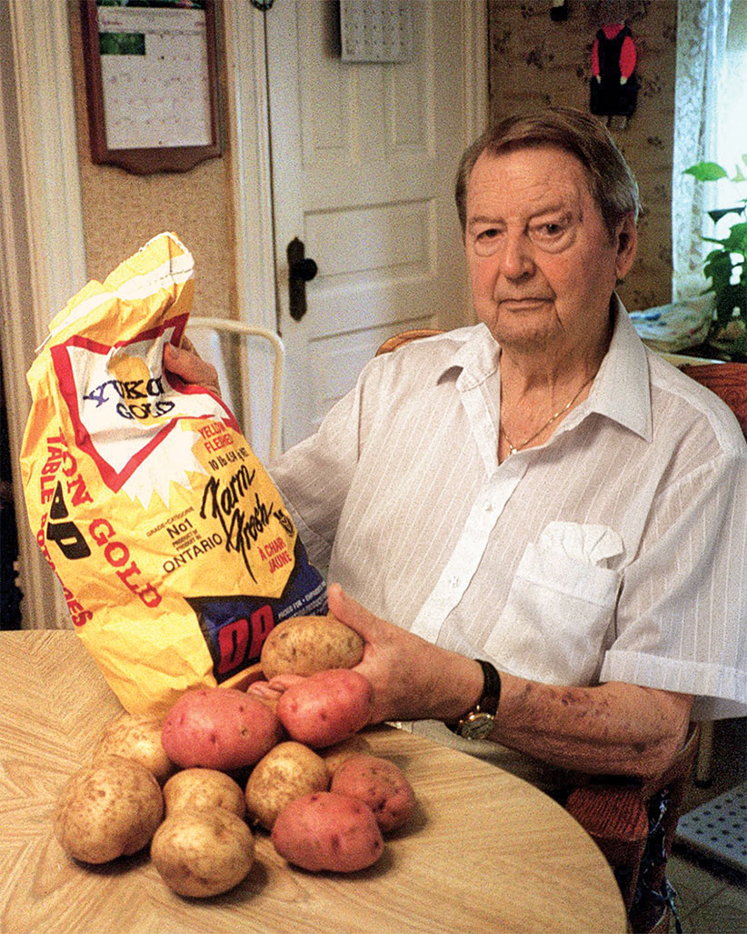 Gary Johnston shows off Yukon Gold and Ruby Gold potatoes in his Guelph, Ont., home. Although retired from the University of Guelph where much of his work as a potato breeder was conducted, the 83-year-old continues to grow and regrow breeding stock from his successful varieties in a greenhouse behind his house. (Judy Creighton/CP)